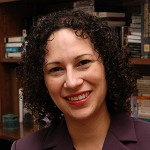 Portait of Rita Cano Alcala. Woman with curly bob-cut black hair smiling. She wears a maroon collared top. In the background there are bookshelves and books.
